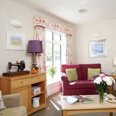 living area with floral curtains at Stowford House Care Home Abingdon